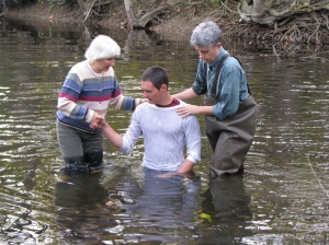 Co-pastors Brenda Meyer and Doug Kaufman baptize Levi Smucker in the Elkhart River.